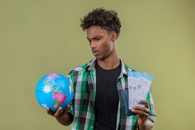 Młody człowiek afroamerykański podróżnik posiadający bilety lotnicze i kula ziemska patrząc na to z poważnym wyrazem twarzy marszcząc brwi stojąc na zielonym tle