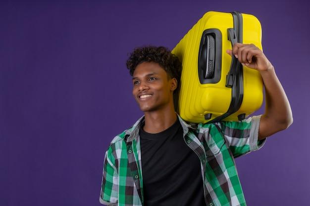Młody człowiek afroamerykański podróżnik trzyma walizkę patrząc na bok uśmiechnięty szczęśliwy i pozytywny stojący na fioletowym tle
