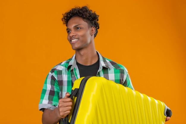 Młody człowiek afroamerykański podróżnik trzyma walizkę patrząc na bok uśmiechnięty szczęśliwy i pozytywny stojący na pomarańczowym tle