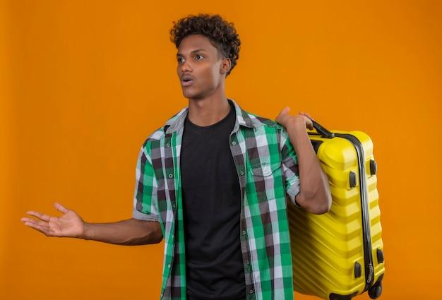 Młody człowiek afroamerykański podróżnik, trzymając walizkę, patrząc na bok zdezorientowany, nie mając odpowiedzi stojącej na pomarańczowym tle