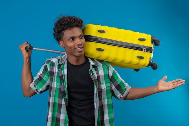 Młody człowiek afroamerykański podróżnik trzymający walizkę patrząc na bok ze zdezorientowanym wyrazem twarzy, gestykuluje ręką, zadając pytanie stojąc na niebieskim tle