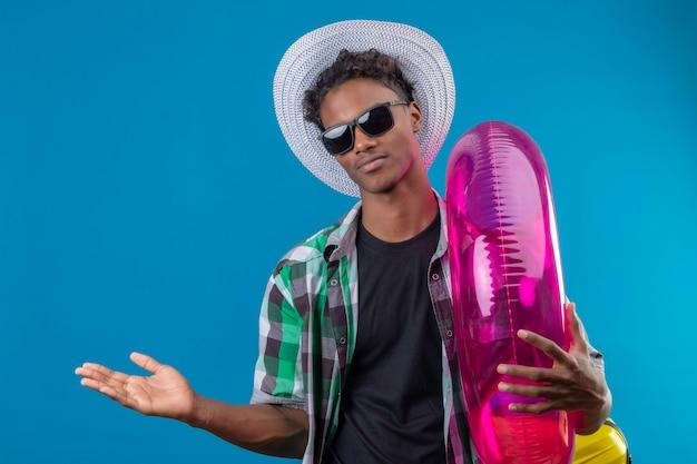 Młody człowiek afroamerykański podróżnik w kapeluszu letnim w czarnych okularach przeciwsłonecznych, trzymając nadmuchiwany pierścień, prezentując ramieniem dłoni kopiuj przestrzeń patrząc na kamerę z pewnym siebie uśmiechem o