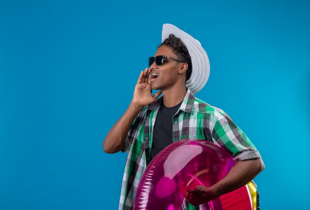 Młody człowiek afroamerykański podróżnik w letnim kapeluszu w czarnych okularach przeciwsłonecznych trzymający nadmuchiwany pierścień patrząc na bok krzycząc lub dzwoniąc do kogoś stojącego na niebieskim tle