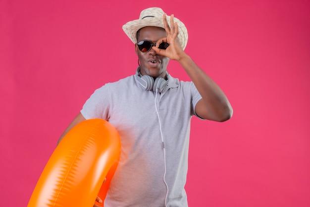 Młody człowiek afroamerykański podróżnik w letnim kapeluszu ze słuchawkami na szyi w czarnych okularach przeciwsłonecznych trzymający nadmuchiwany pierścień robi ok, śpiewając, patrząc przez to śpiewając na różowym