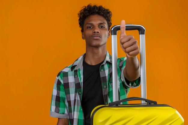 Młody człowiek afroamerykański podróżnik z walizką z pewną poważną miną na twarzy pokazując kciuk do góry