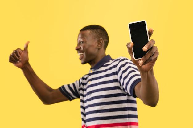 Młody człowiek afroamerykański z smartphone na białym tle na żółtym tle studio, wyraz twarzy. piękny portret męski do połowy długości. pojęcie ludzkich emocji, wyraz twarzy.