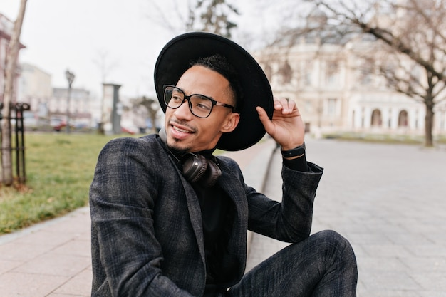 Młody człowiek afryki, ciesząc się dobry wiosenny dzień w parku. odkryty zdjęcie niesamowitego mulata modela siedzącego na placu i czekającego na kogoś.