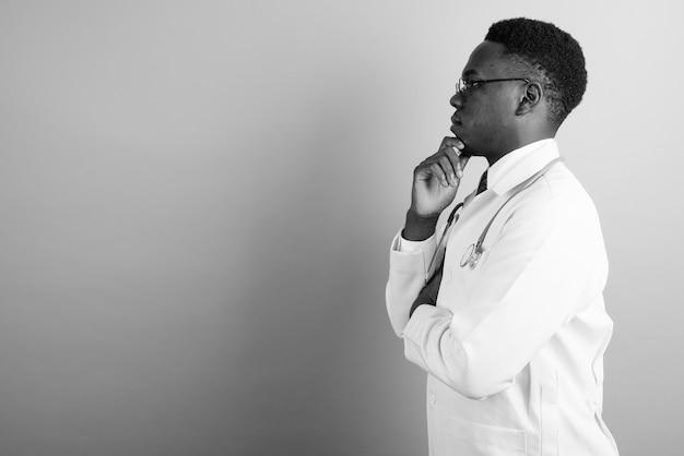 Młody człowiek afryki lekarz noszenie okularów przed białą ścianą. czarny i biały