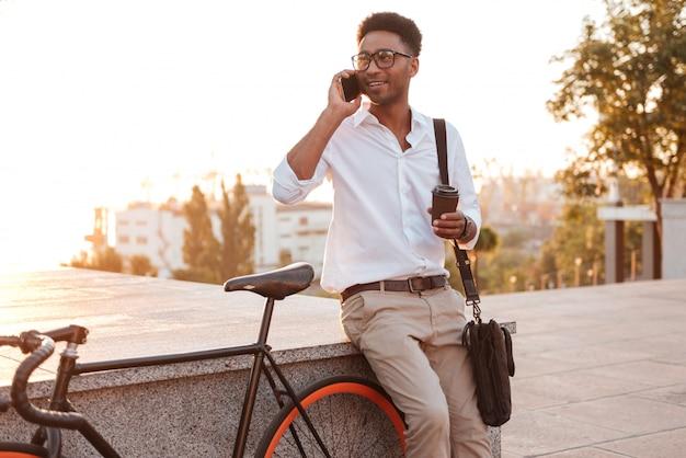 Młody człowiek afryki rano z rowerem rozmawia przez telefon.