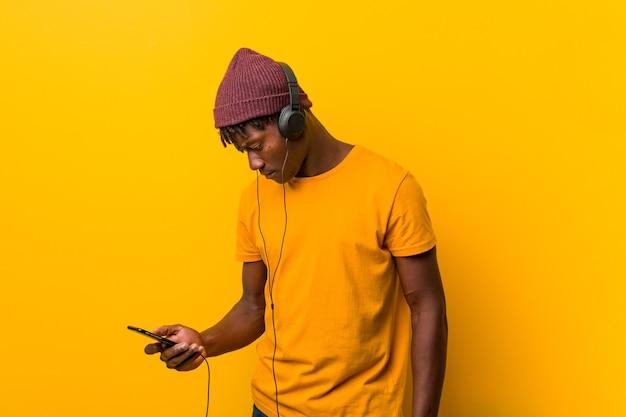 Młody człowiek afryki stojącej przed żółtą przestrzenią w kapeluszu, słuchanie muzyki przez telefon