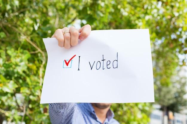 Młody człowiek, aktywista wzywa do głosowania, trzymając w ręku papier z oświadczeniem głosowałem. aktywizm polityczny, proces wyborczy, koncepcja pozycji aktywnego życia. prezydent, wybory do konstytucji.