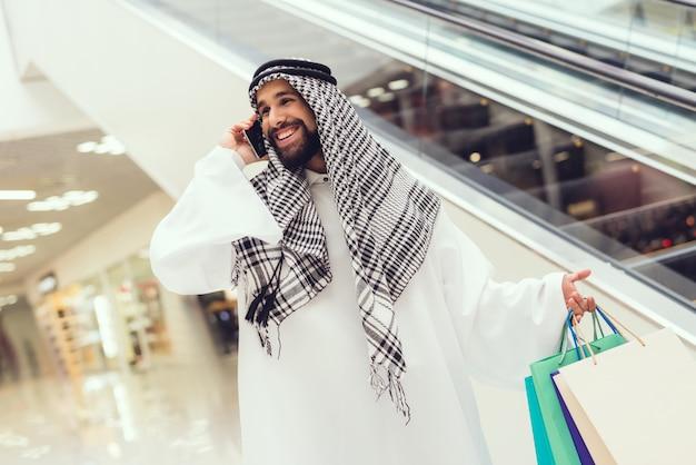 Młody człowiek arabian przy użyciu telefonu komórkowego w nowoczesnym centrum handlowym.