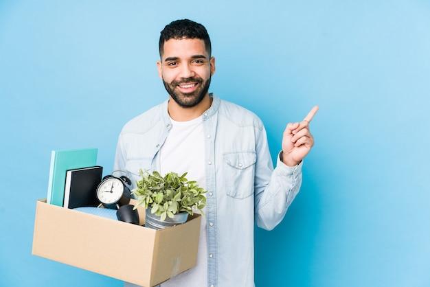 Młody człowiek arabski przeprowadzki do nowego domu, uśmiechając się i wskazując na bok, pokazując coś w pustej przestrzeni.