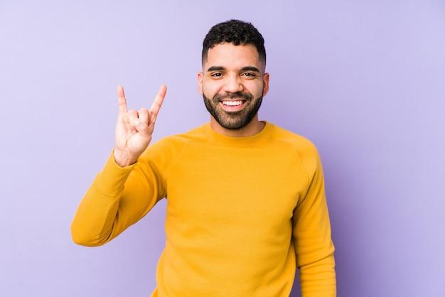 Młody człowiek arabski rasy mieszanej na białym tle przedstawiający gest rogów jako koncepcja rewolucji.