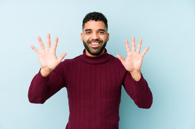 Młody człowiek arabski rasy mieszanej na białym tle wyświetlono numer dziesięć rękami.