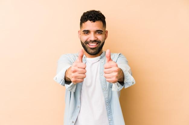 Młody człowiek arabski rasy mieszanej na białym tle z kciuki w górę, wiwatuje o czymś, koncepcja wsparcia i szacunku.