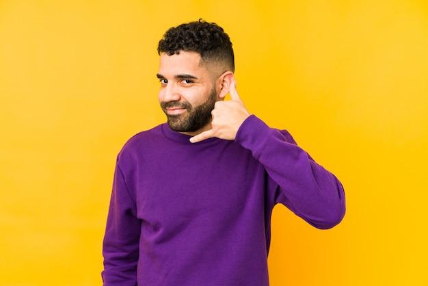 Młody człowiek arabski rasy mieszanej pokazano gest telefonu komórkowego palcami.