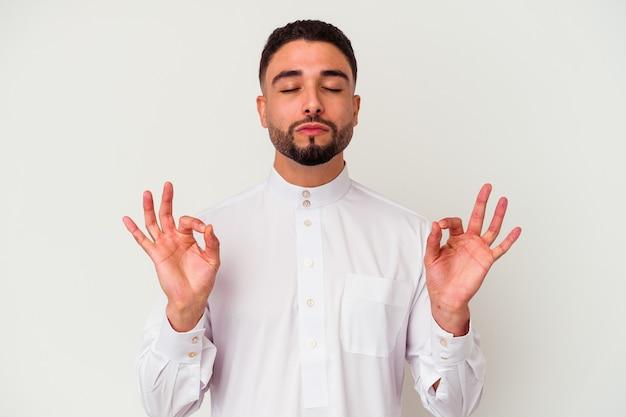 Młody człowiek arabski ubrany w typowe arabskie ubrania na białym tle relaksuje się po ciężkim dniu pracy, ona wykonuje jogę.