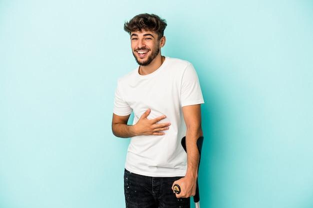 Młody człowiek arabski z kulami na białym tle na niebieskim tle śmiechu i zabawy.