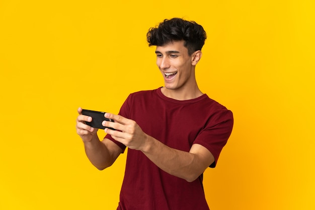 Młody człowiek argentyński na białym tle na żółtej ścianie, grając z telefonem komórkowym