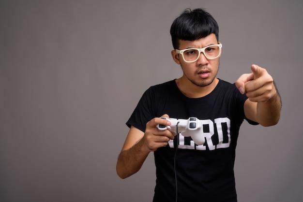 Młody człowiek azjatyckich frajerem noszenie okularów przeciwko szarości