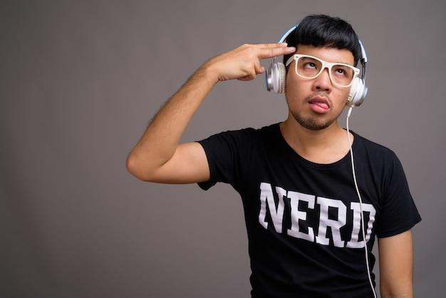 Młody człowiek azjatyckich frajerem słuchania muzyki przeciwko szarości