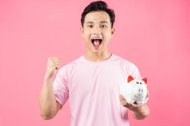 Młody człowiek azjatyckich gospodarstwa skarbonka na różowo