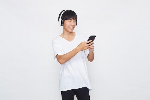 Młody człowiek azjatyckich noszenie słuchawek ze smartfona na białym tle