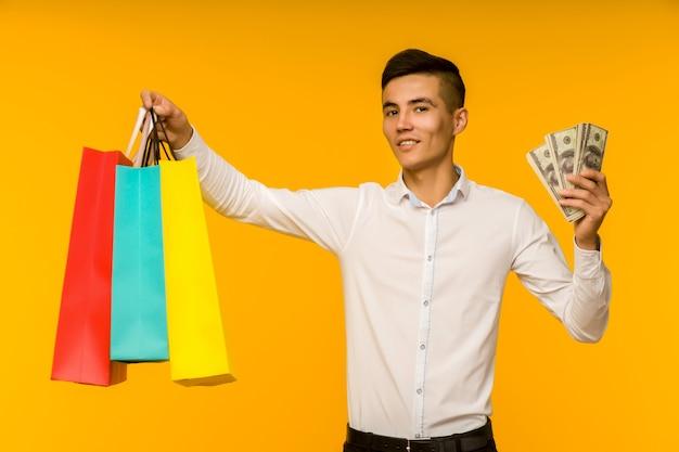 Młody człowiek azjatyckich pokazując torbę na zakupy i pieniądze na żółtej przestrzeni