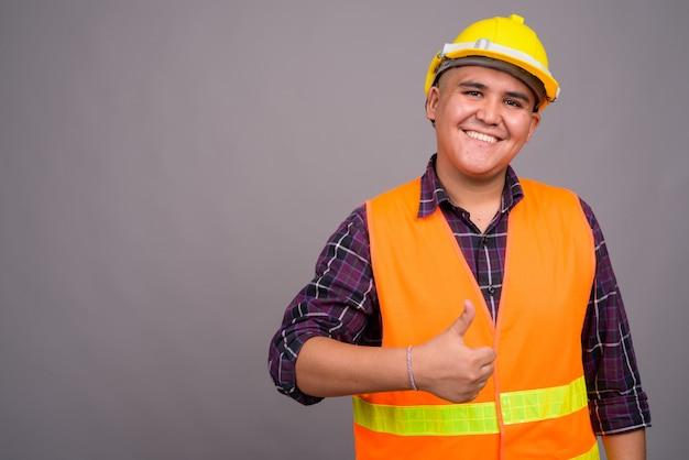 Młody człowiek azjatyckich pracownik budowlany przed szarej ścianie