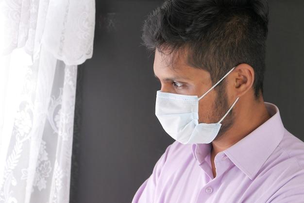 Młody człowiek azjatyckich z maską ochronną w twarz patrząc przez okno