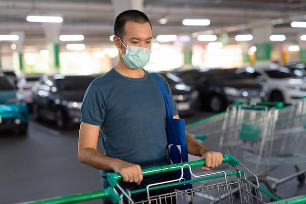 Młody człowiek azjatyckich z maską trzymając koszyk na parkingu