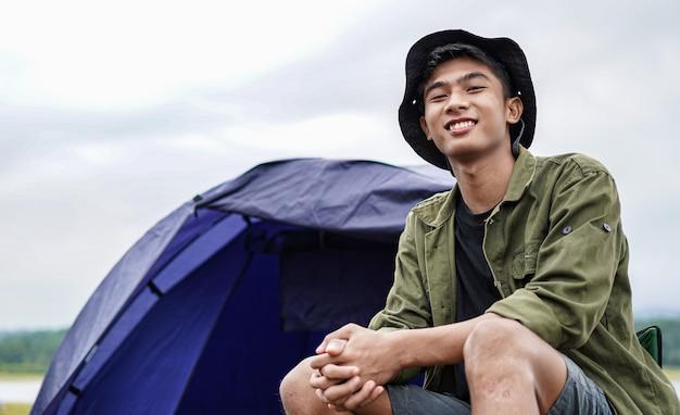 Młody człowiek azji cieszyć się kempingiem w zbiorniku