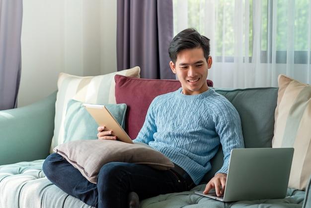 Młody człowiek azji na spokojny dzień siedzi w domu na kanapie za pomocą laptopa i tabletu na kanapie.