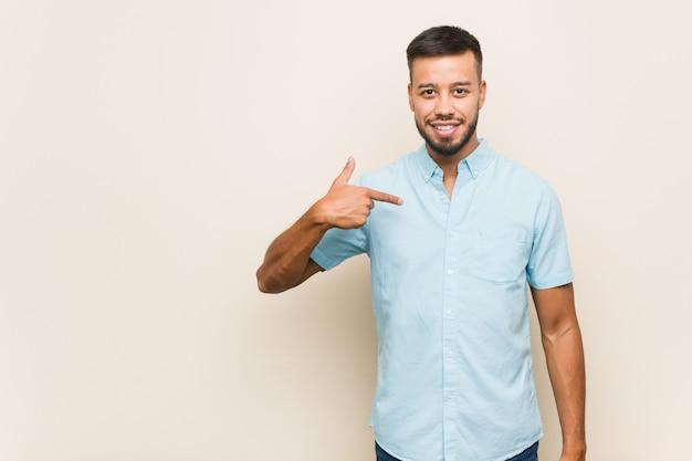 Młody człowiek azji południowo-azjatyckiej, wskazując ręką na miejsce kopii koszuli, dumny i pewny siebie