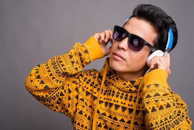 Młody człowiek azji, słuchając muzyki, mając na sobie bluzę z kapturem na szarej ścianie
