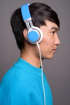 Młody człowiek azji, słuchanie muzyki na szarej ścianie
