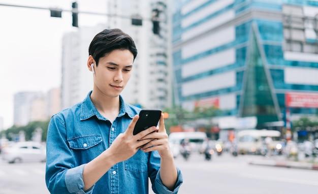 Młody człowiek azji, spacery i używanie smartfona na ulicy