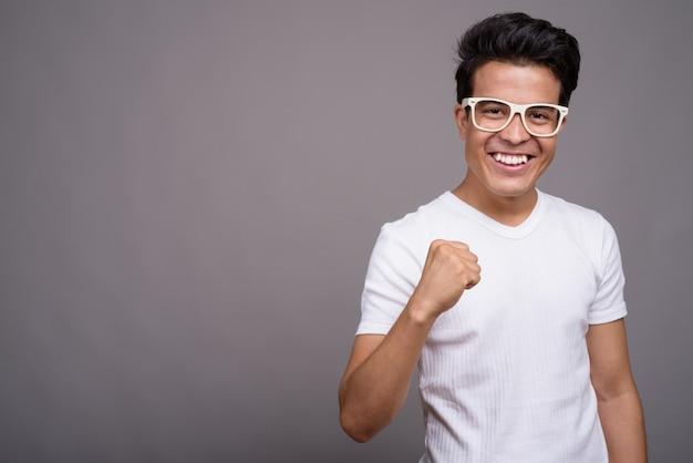 Młody człowiek azji ubrany w białą koszulę i okulary