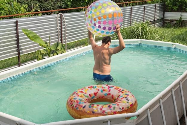 Młody człowiek bawi się na basenie z pontonami