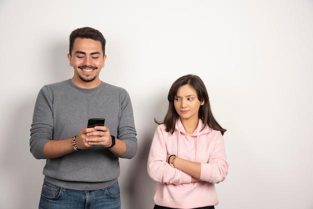 Młody człowiek bawi się telefonem, podczas gdy jego kochanek patrzy.
