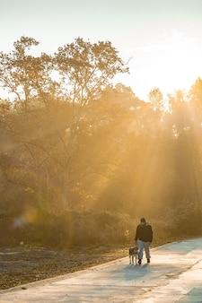 Młody człowiek bawi się z psem na łonie natury z promieniami porannego słońca kocham mojego psa