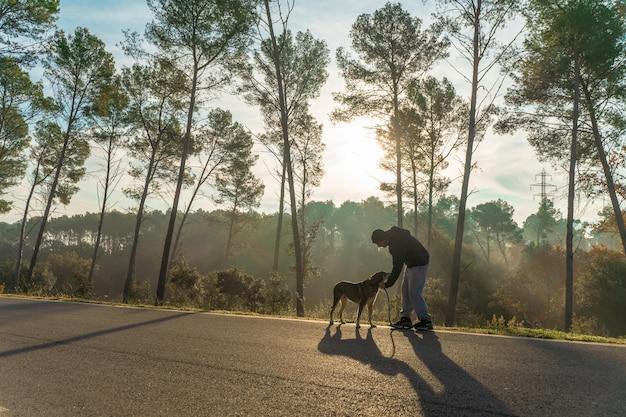 Młody człowiek bawi się z psem na łonie natury z promieniami porannego słońca