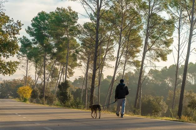 Młody człowiek bawi się ze swoim psem na łonie natury z ciepłymi promieniami porannego słońca