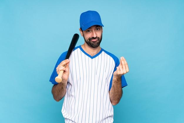 Młody człowiek bawić się baseballa nad odosobnioną błękit ścianą robi pieniądze gestowi