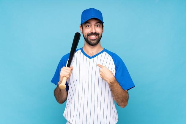 Młody człowiek bawić się baseballa nad odosobnioną błękit ścianą z niespodzianka wyrazem twarzy