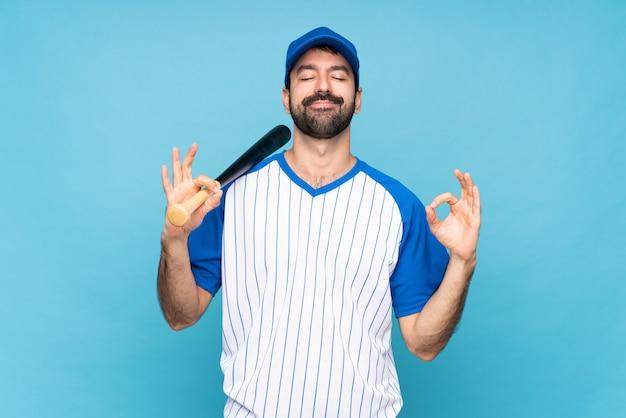 Młody człowiek bawić się baseballa nad odosobnionym błękitem w zen pozie