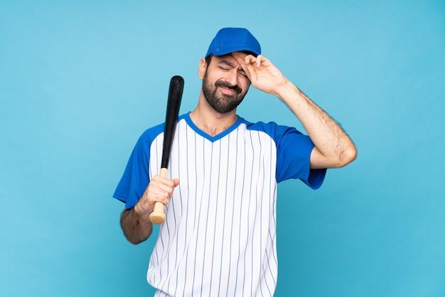 Młody człowiek bawić się baseballa nad odosobnionym błękitem z zmęczonym i chorym wyrażeniem
