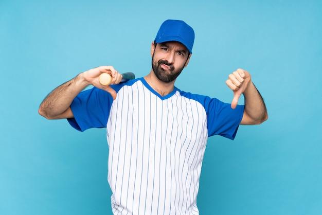 Młody człowiek bawić się baseballa nad odosobnionym błękitnym pokazuje kciuka puszkiem
