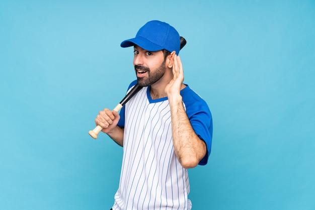 Młody człowiek bawić się baseballa nad odosobnionym błękitnym słuchaniem coś kładzenie ręka na ucho